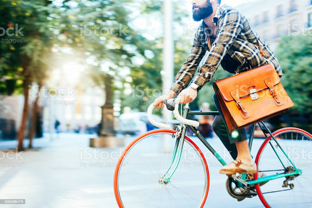 Young hipster man speeding with his bike. stock photo