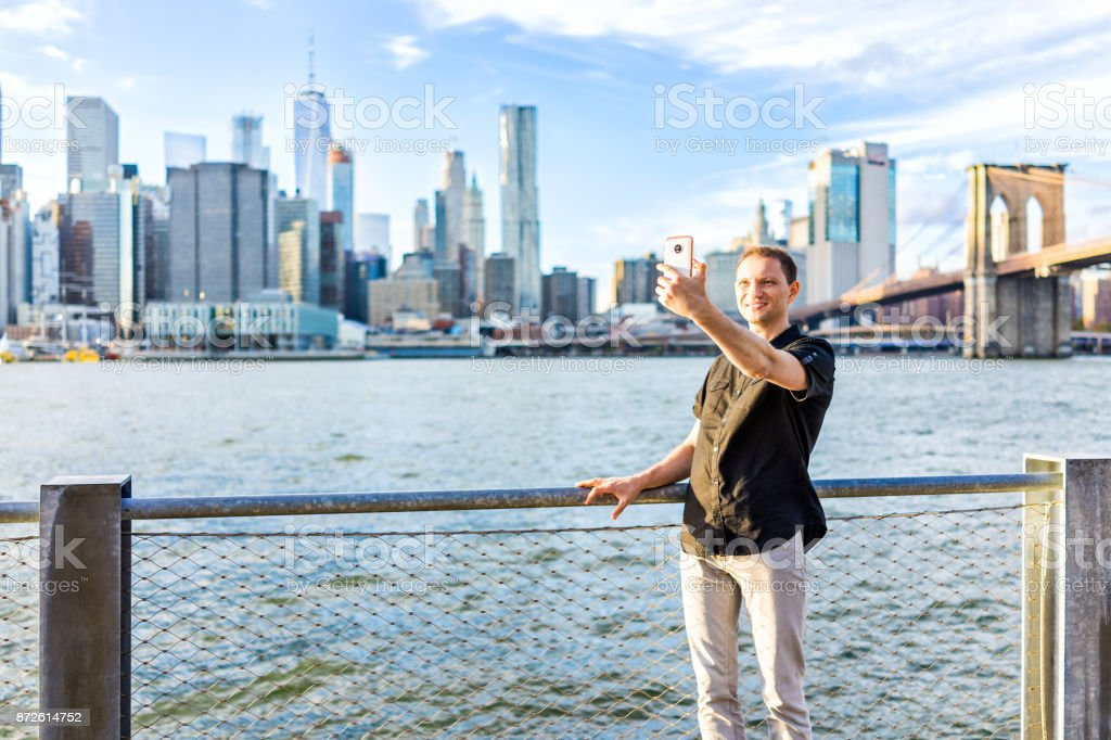 Young hipster man standing taking selfie picture by fence in Brooklyn Bridge Park overlooking the NYC New York City Manhattan cityscape skyline with water bay during sunset stock photo