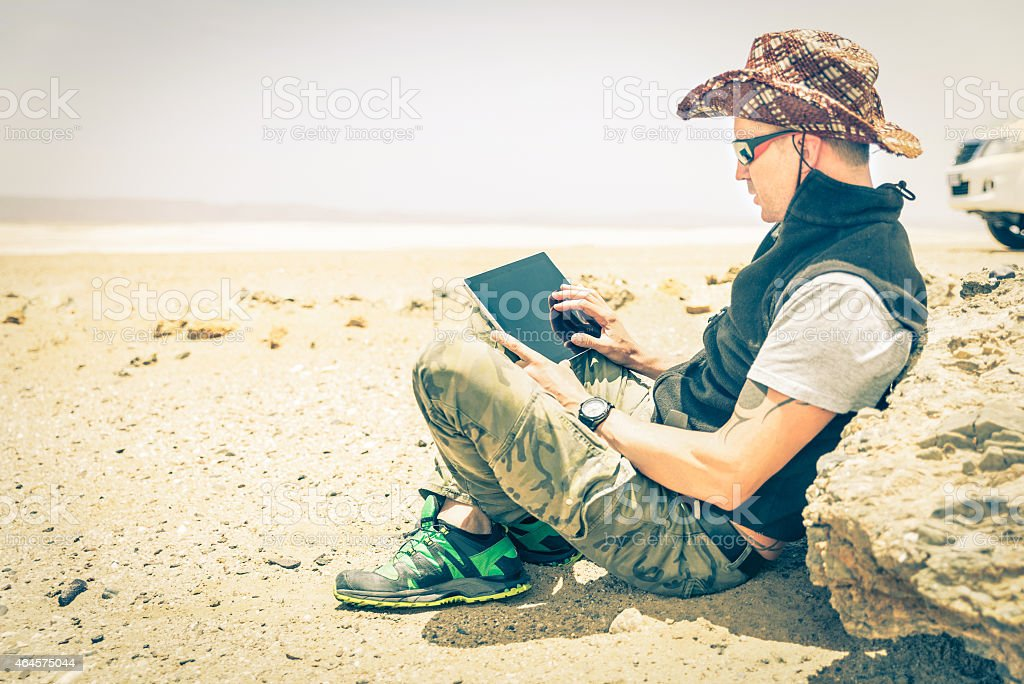 Young hipster man using tablet on desert road stock photo