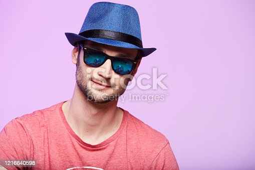 istock Young hipster man wearing blue hat. Studio shot over pink background. 1216640598