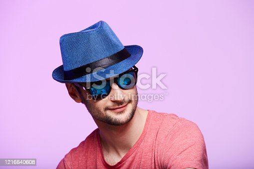 istock Young hipster man wearing blue hat. Studio shot over pink background. 1216640608