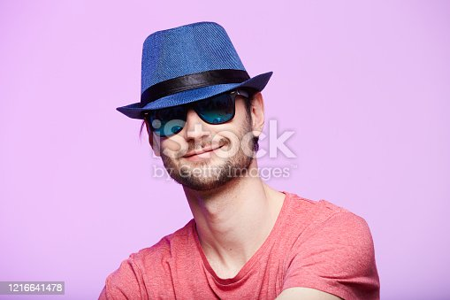 istock Young hipster man wearing blue hat. Studio shot over pink background. 1216641478