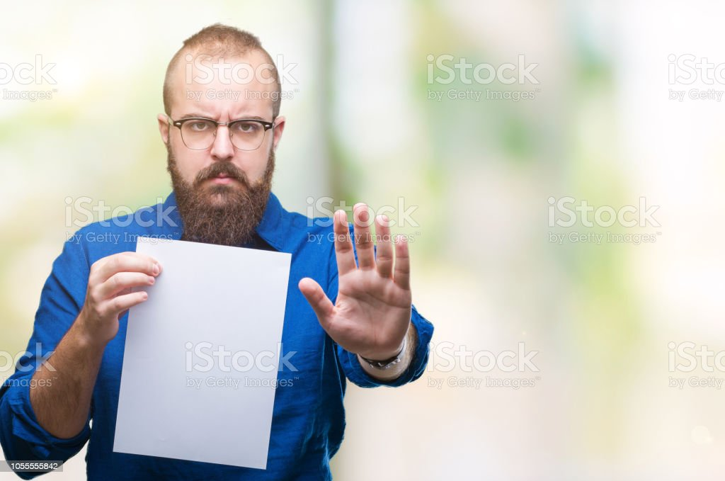 Young hipster man wearing glasses and holding blank paper over isolated background with open hand doing stop sign with serious and confident expression, defense gesture stock photo