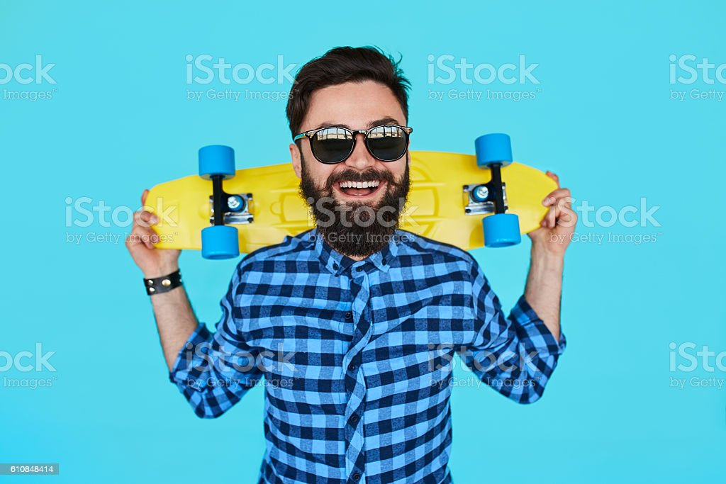 Young hipster man with a skateboard stock photo