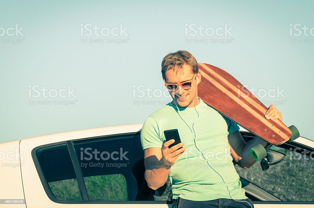 Young hipster man with car and smartphone listening music stock photo