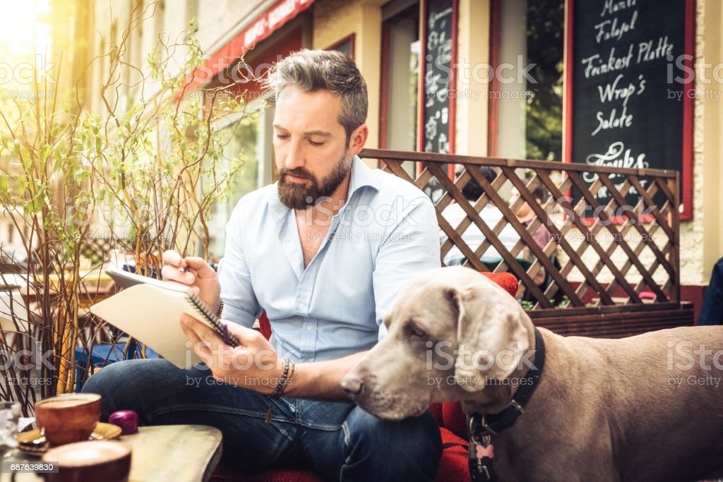 Young hipster man with dog sketching in street cafe stock photo
