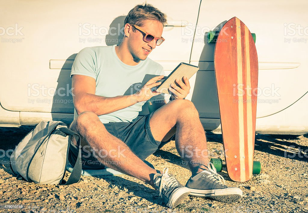 Young hipster man with tablet sitting next his car stock photo