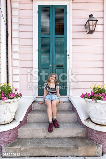 Young hipster millennial woman sitting smiling happy on stairs steps, front porch in New Orleans by colorful pink door architecture during day with yellow flowers in spring and summer pot