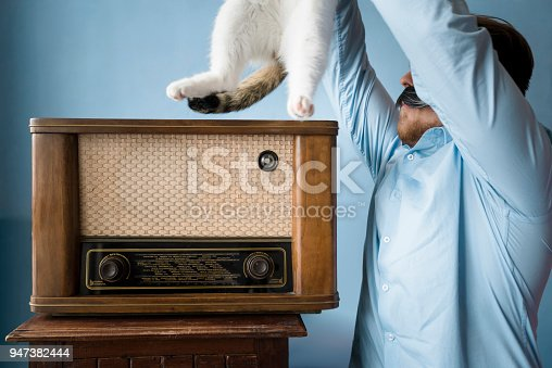 Young hipster placing his cat on top of old-style radio. Man with fake whiskers holding white cat in the air, located in Varna, Bulgaria.