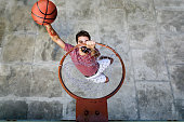 A DSLR Canon photo of a young hipster player dunking basketball in the hoop.