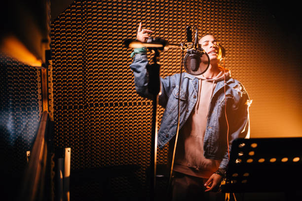 Young hipster rap music singer recording song in music studio stock photo