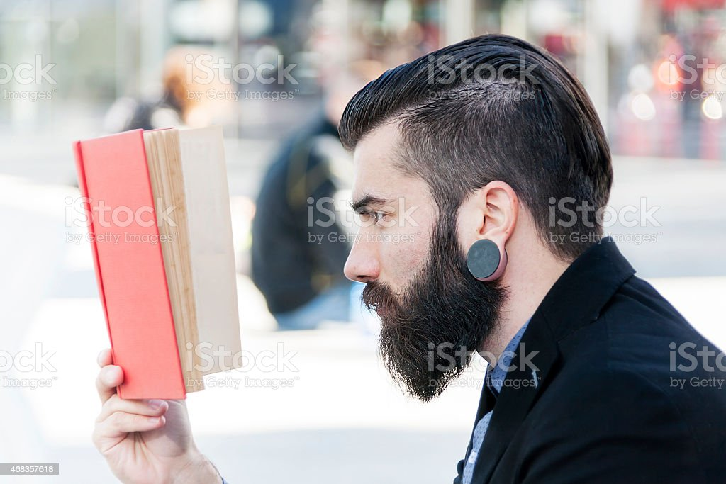 young hipster reading a book sitting outdoors royalty-free stock photo