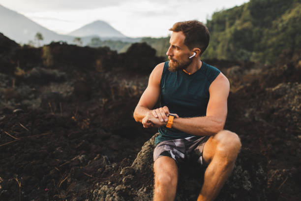 Young hipster runner with beard using smart watch and listening music in wireless headphones before running outdoors. Young hipster runner with beard using smart watch and listening music in wireless headphones before running outdoors. wireless headphones stock pictures, royalty-free photos & images