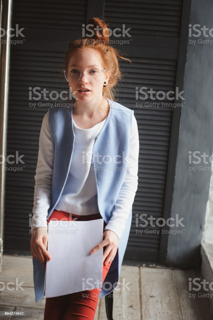 young hipster student woman or creative freelance designer working on project. Holding coursework or business plan. stock photo