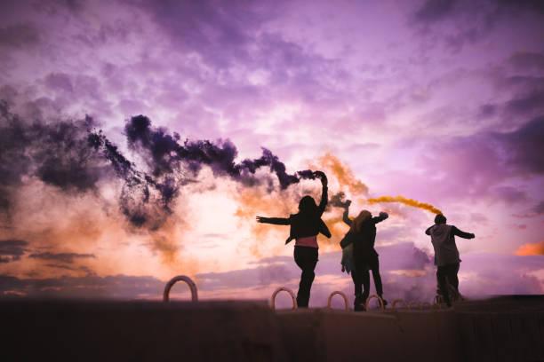 junge hipster jugendliche feiern mit rauchbomben - lila waffe stock-fotos und bilder