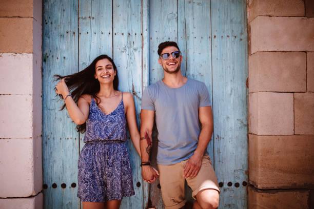 junge hipster-touristen paar hand in hand gegen alte tür - hochzeitsreise zypern stock-fotos und bilder