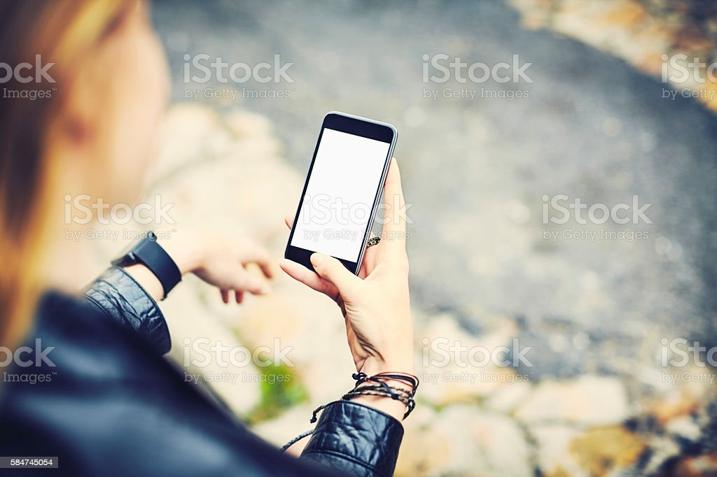 Young hipster using smart phone with blank screen outdoors stock photo