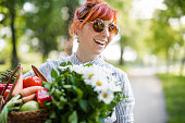 Young hipster woman holding basket full of groceries and flowers, in nature on sunny summer day
