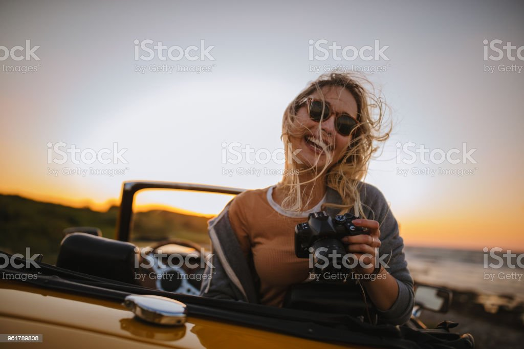 Young hipster woman in convertible car taking photos at sunset royalty-free stock photo