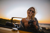 Young hipster woman in convertible car taking photos at sunset