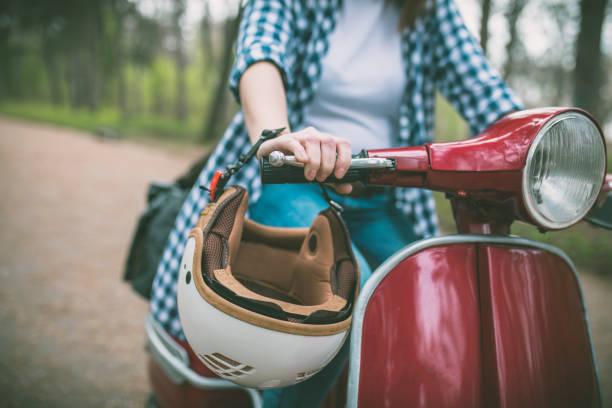 mujer joven inconformista en casco sentado en un scooter vintage. - vintage vespa fotografías e imágenes de stock