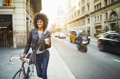 Young hipster woman in the streets of Barcelona commuting. Mixed race model, spanish and Ethiopian.