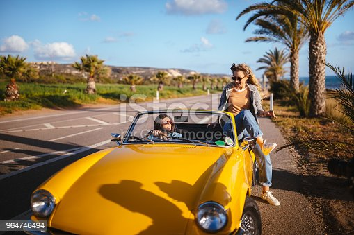 Hipster women ready for road trip summer holidays on exotic island with retro cabriolet car