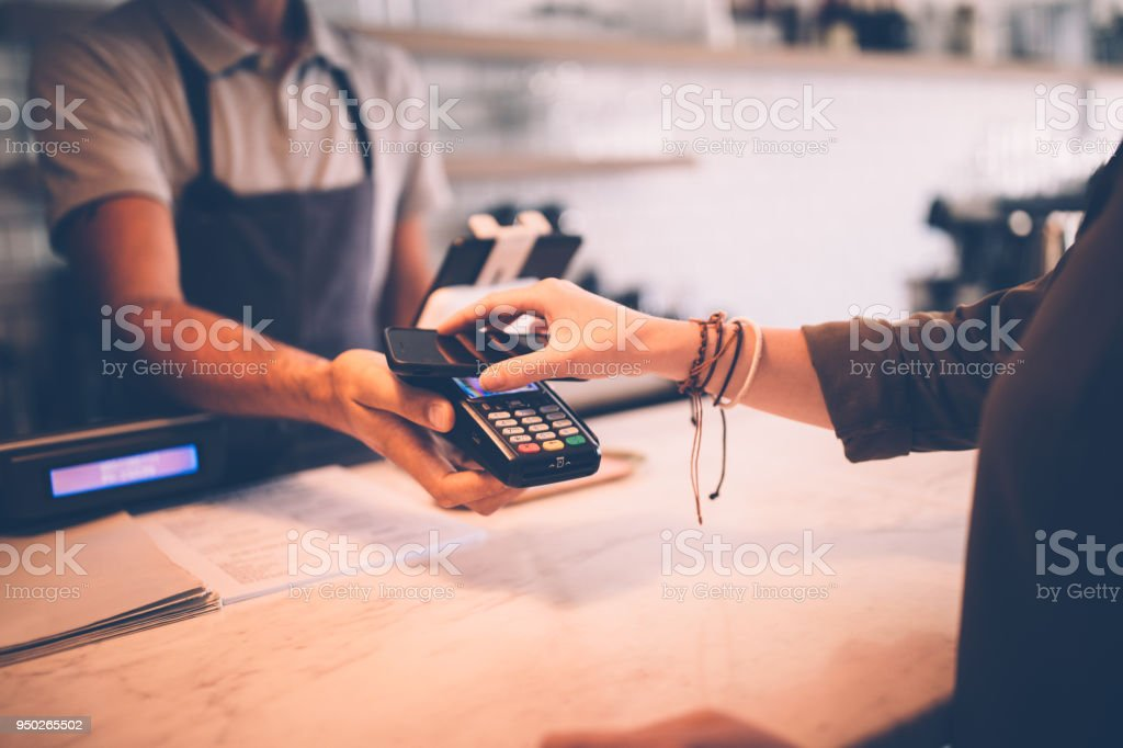 Young hipster woman paying using NFC smartphone contactless technology stock photo