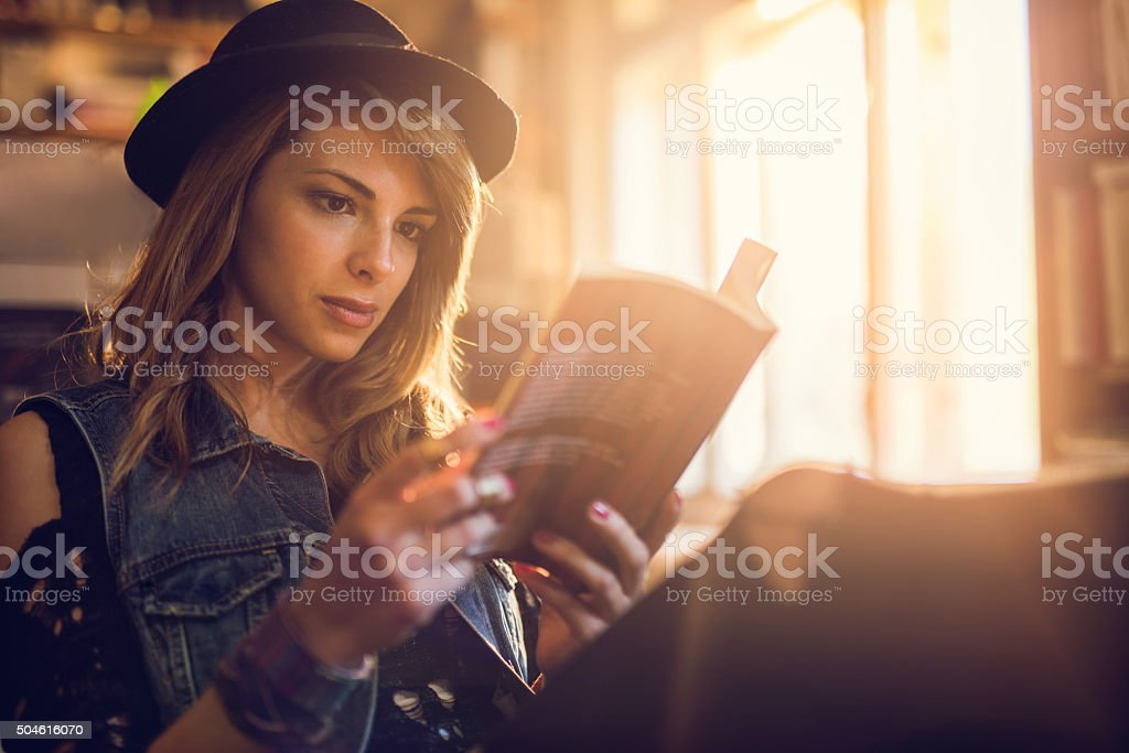 Young hipster woman relaxing while reading a book. stock photo