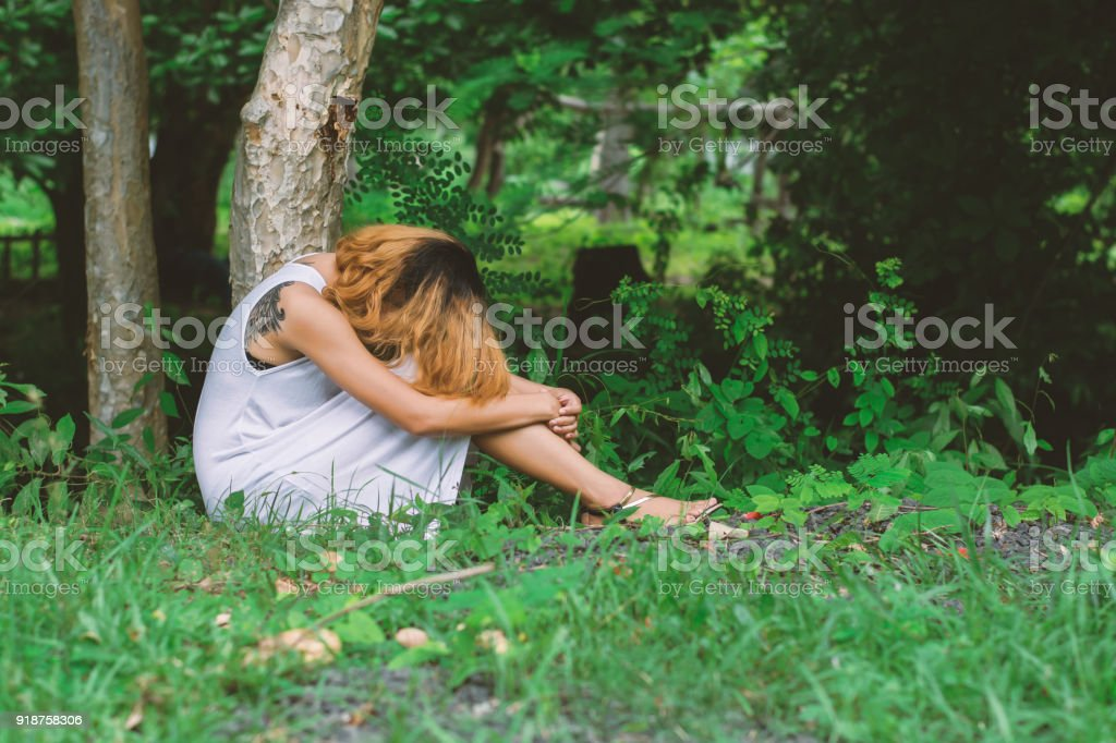 young hipster woman, sad, long-haired  sitting hugging legs. stock photo