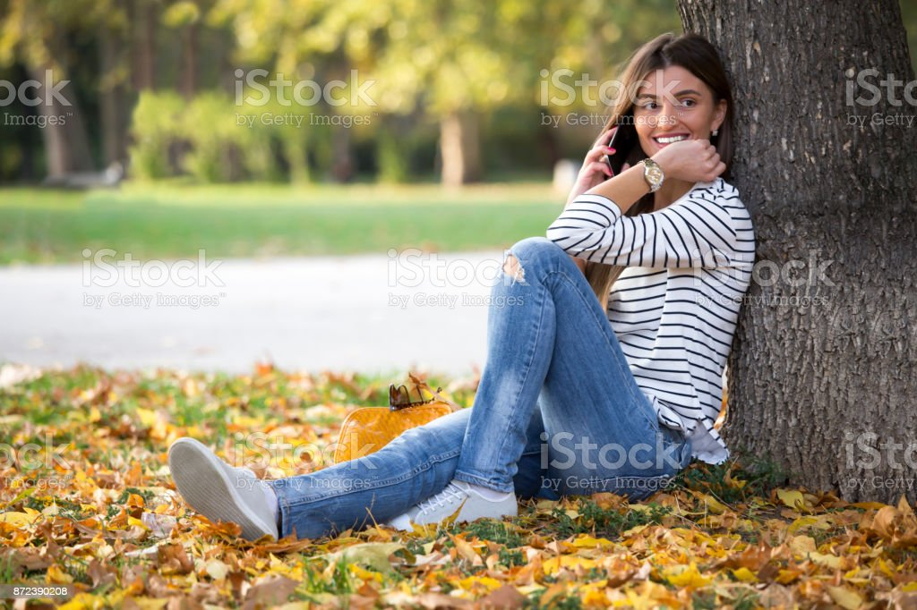 Young hipster woman sitting in a park, and talking on a phone stock photo