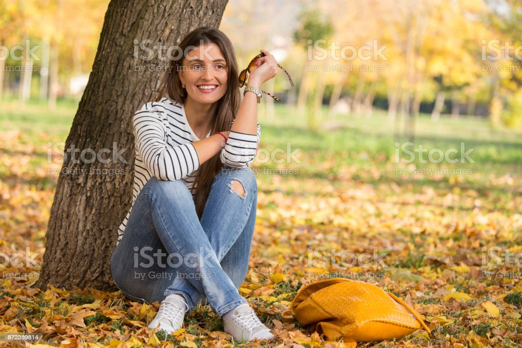 Young hipster woman sitting in a park, autumn stock photo