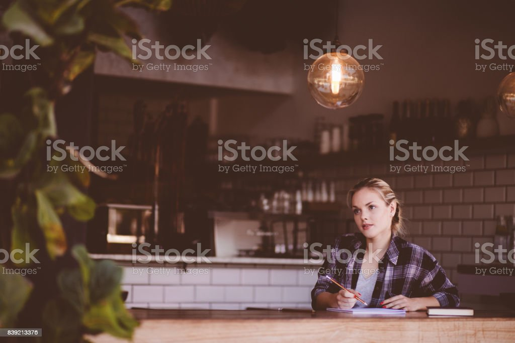 Young hipster woman studying in urban cafe stock photo