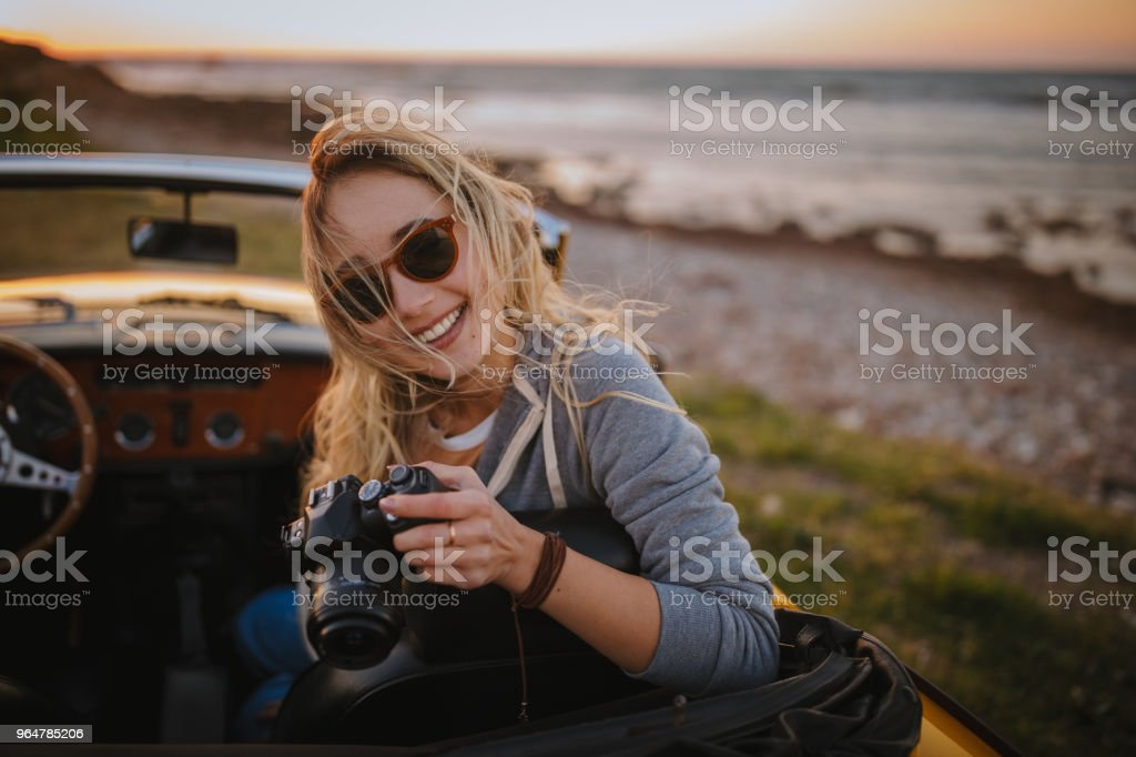 Young hipster woman taking photos in vintage cabriolet car royalty-free stock photo