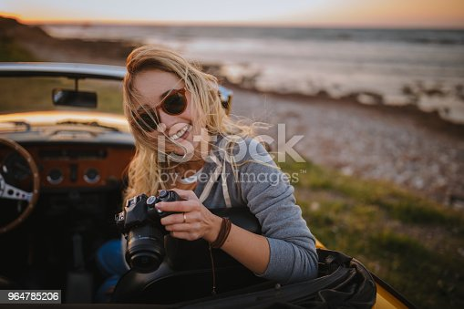 147878016 istock photo Young hipster woman taking photos in vintage cabriolet car 964785206