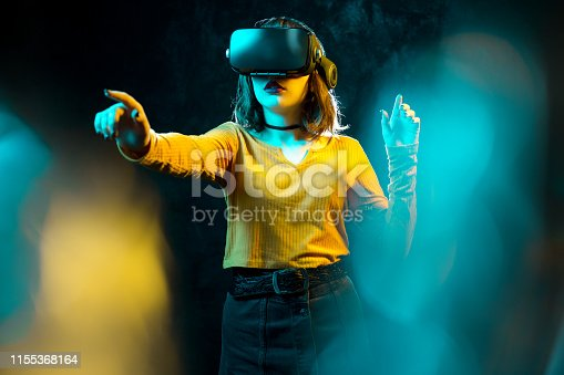 istock Young hipster woman with curly hair wearing virtual reality goggles and touch another world in studio neon lights. Smartphone using with VR headset. 1155368164