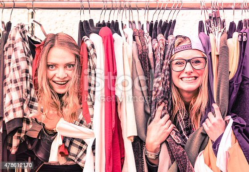 Young hipster women at clothes flea market - Best friends sharing fun time shopping in the city - Urban girlfriends enjoying happy life moments - Soft focus on vintage pink marsala filtered look