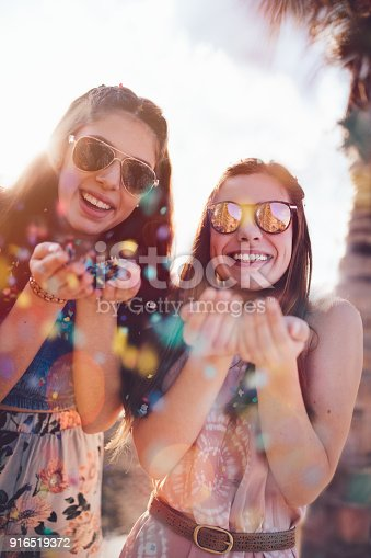 699427744 istock photo Young hipster women celebrating with confetti on summer holidays 916519372