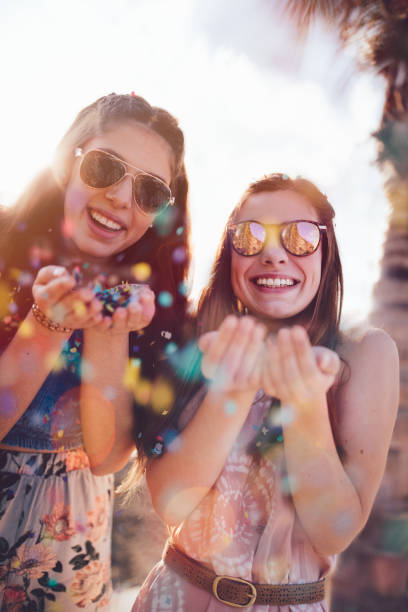 young hipster women celebrating with confetti on summer holidays - beach fashion stock photos and pictures