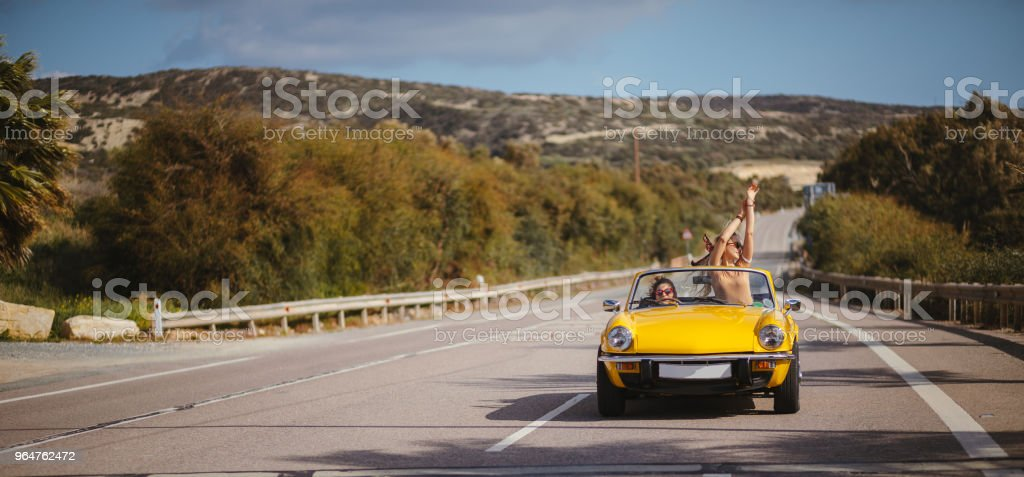 Young hipster women driving vintage convertible car on highway royalty-free stock photo