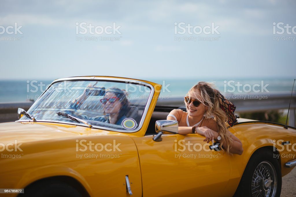 Young hipster women enjoying ride in vintage convertible car royalty-free stock photo