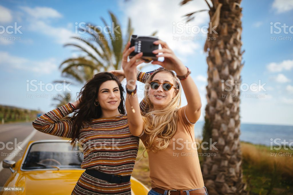Young hipster women taking selfies on summer holidays road trip royalty-free stock photo