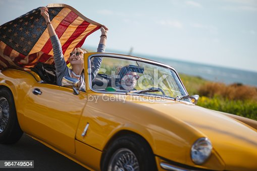 Young hipster girls driving retro convertible car and celebrating fourth of July with Amerian flag