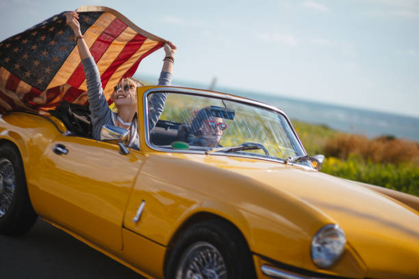 Young hipster women with American flag driving retro convertible car Young hipster girls driving retro convertible car and celebrating fourth of July with Amerian flag independence day holiday stock pictures, royalty-free photos & images