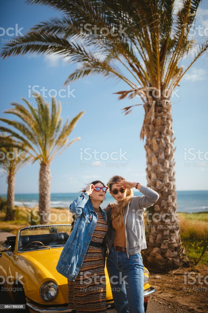 Young women with convertible car standing by the road royalty-free stock photo