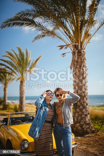 Young hipster women with broken retro convertible car waiting for help at road side