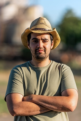 Young hispanic agricultural worker immigrant posing looking at the camera