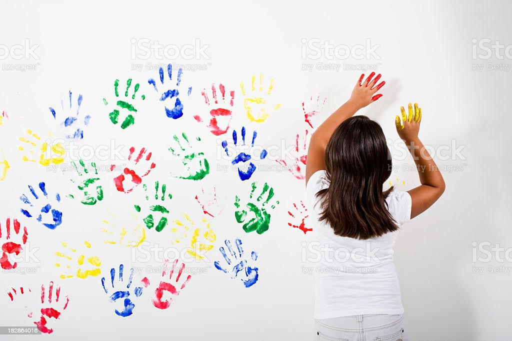 Young Hispanic Asian girl playing with finger paints stock photo