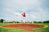 Low angle view of Hispanic baseball pitcher standing on the mound in wind-up position preparing to throw the ball.