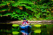 Young Hispanic boy out fishing in his kayak in a lake